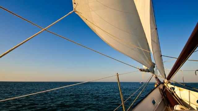 Sailboat navigating towards sunset at bonaire regatta