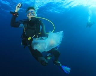 Scuba diver cleans up plastic rubbish pollution discarded in ocean - dive clean-up Bonaire